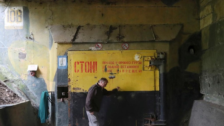 In this picture taken on Wednesday, Sept. 21, 2016, a man opens a door at a museum of the Cold War nuclear arms race located at the Brdy reserve in Brdy, Czech Republic. In the deep forests of Brdy, there's a unique concrete installation known under the code name Javor (Maple) 51 which is believed to be used by the Soviet Army as a top secret depot to store nuclear war heads during the Cold War. A former military zone near Prague has been turning into a protected nature reserve and opening to the public after almost a century. (AP Photo/Petr David Josek)