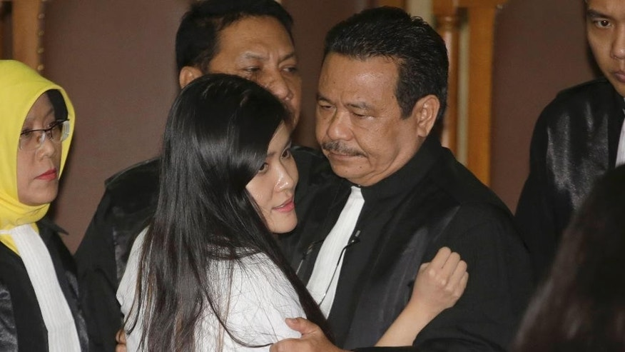 Jessica Kumala Wongso is comforted by her lawyer Otto Hasibuan after her sentence at a courtroom of Central Jakarta District Court in Jakarta, Indonesia, Thursday, Oct. 27, 2016. The former Australian resident is accused of killing her friend Wayan Mirna Salihin with a cyanide-laced coffee to 20 years in prison in a dramatic climax to a trial that was broadcast live and became a national spectacle. (AP Photo/Tatan Syuflana)