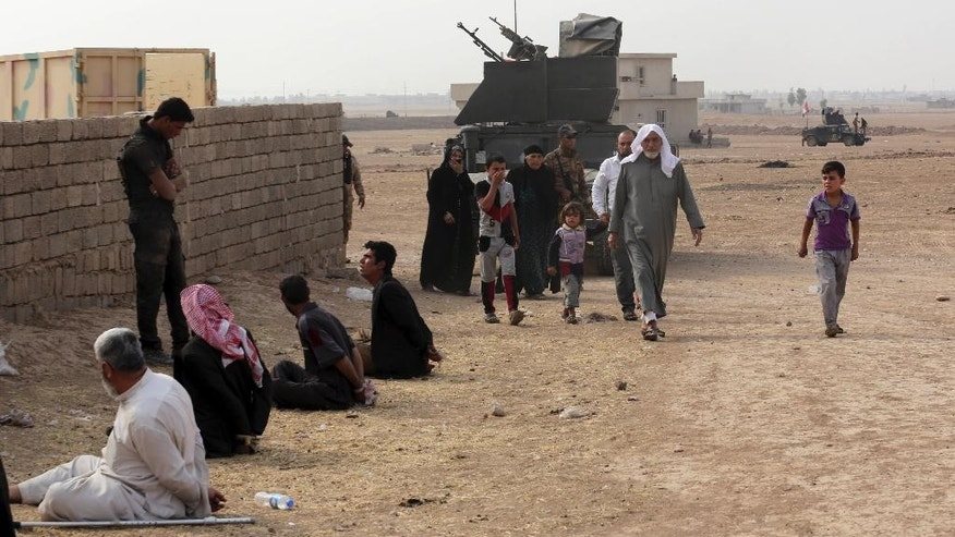In this Tuesday, Oct. 25, 2016 photo, civilians leave their houses as a member of Iraq's elite counterterrorism forces interrogates handcuffed people that are suspected to be supporters of the Islamic State group, in the village of Tob Zawa, about 9 kilometers (5½ miles) from Mosul, Iraq. Around 335 civilians were evacuated to a refugee camp from the village, which was retaken by special forces on Monday, Maj. Gen. Haider Fadhil said. He said the civilians were relocated to protect them from possible IS shelling. (AP Photo/Khalid Mohammed)
