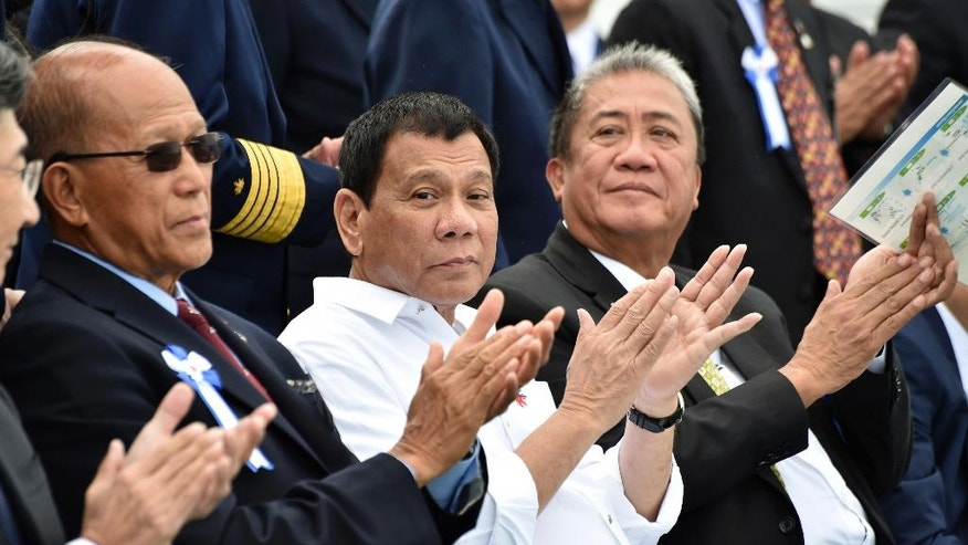Philippine President Rodrigo Duterte, center, accompanied by Transportation Secretary Arthur Tugade, right, and Defense Secretary Delfin Lorenzana, left, clap their hands at the end of Japan's coast guard drills in Yokohama Thursday, Oct. 27, 2016.  Duterte is on a three-day official visit to Japan, his first as Philippine leader. (Kazuhiro Nogi/Pool Photo via AP)