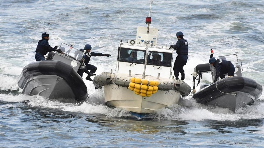 Japan Coast Guard security team display tracking and capture drills by rigid-hulled inflatable boats against an unidentified ship at sea in Yokohama Thursday, Oct. 27, 2016 while Philippine President Rodrigo Duterte inspect. (Kazuhiro Nogi/Pool Photo via AP)