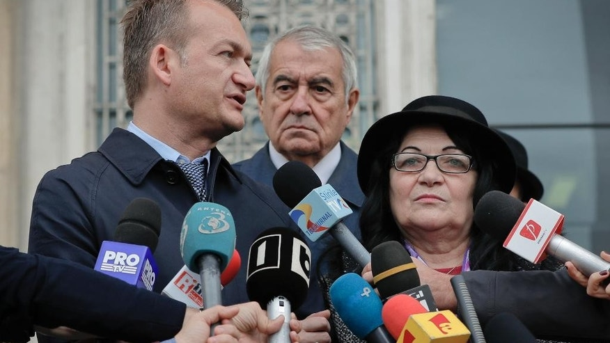 Adrian Coman, left, speaks outside the Constitutional Court, next to his parents Camelia and Liviu Coman in Bucharest, Romania, Thursday, Oct. 27, 2016. Coman is asking the Constitutional Court to recognize his 2010 marriage in Belgium to a U.S. citizen Claibourn Robert Hamilton, in a case that has pitted a conservative majority against those who seek closer integration into the European mainstream. (AP Photo/Vadim Ghirda)
