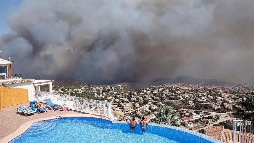 FILE - In this Monday, Sept. 5, 2016 file photo, two men look out from a swimming pool at a wildfire as it burns nearby Benitachel village, eastern Spain. Scientists say southern Spain will become desert and deciduous forests will vanish from much of the Mediterranean basin unless global warming is reined in sharply. They concluded that any warming above 2 degrees Celsius would cause changes not seen in 10,000 years. (AP Photo/Alberto Saiz, file)