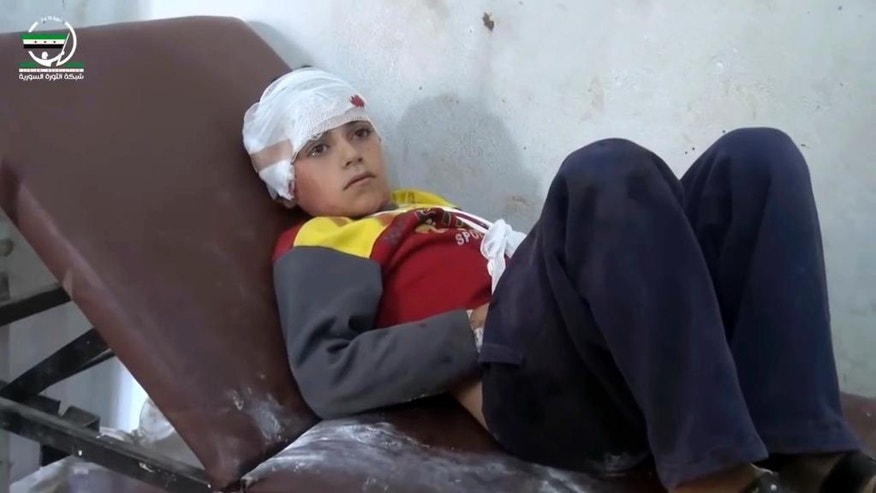 This frame grab from video provided by Muaz al-Shami, Syrian Revolution Network, an opposition activist media organization, that is consistent with independent AP reporting, shows a child on a hospital bed, with a bandage around his head after airstrikes killed over 20 people, in the northern rebel-held village of Hass, Syria, Wednesday, Oct 26, 2016. A team of first responders, the Syrian Civil Defense in Idlib, said at least 50 were wounded in the raids that used parachute mines, targeting the residential area and schools in the village of Hass.  Most of those killed were children, the group said on its Facebook page. (Muaz al-Shami, Syrian Revolution Network, via AP)