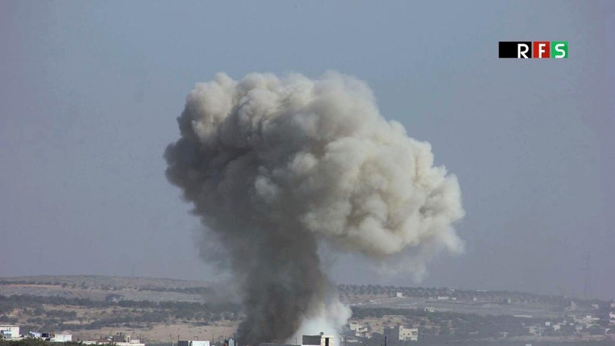 This photo provided by the Revolutionary Forces of Syria, an opposition activist media organization, which has been authenticated based on its contents and other AP reporting, shows an airstrike that killed over 20 people in the village of Hass, Syria, Wednesday, Oct 26, 2016. A team of first responders, the Syrian Civil Defense in Idlib, said at least 50 were wounded in the raids that used parachute mines, targeting the residential area and schools in the village of Hass. Most of those killed were children, the group said on its Facebook page.  (Revolutionary Forces of Syria, via AP)