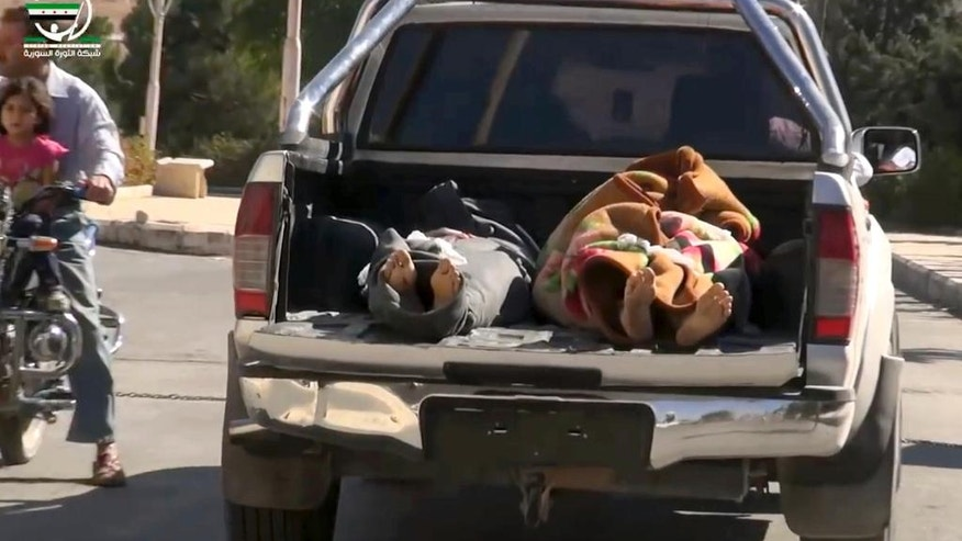 This frame grab from video provided by Muaz al-Shami, Syrian Revolution Network, an opposition activist media organization, that is consistent with independent AP reporting, shows two bodies lying down in the open back of a pick-up truck after airstrikes killed over 20 people, in the northern rebel-held village of Hass, Syria, Wednesday, Oct 26, 2016. A team of first responders, the Syrian Civil Defense in Idlib, said at least 50 were wounded in the raids that used parachute mines, targeting the residential area and schools in the village of Hass.  Most of those killed were children, the group said on its Facebook page. (Muaz al-Shami, Syrian Revolution Network, via AP)