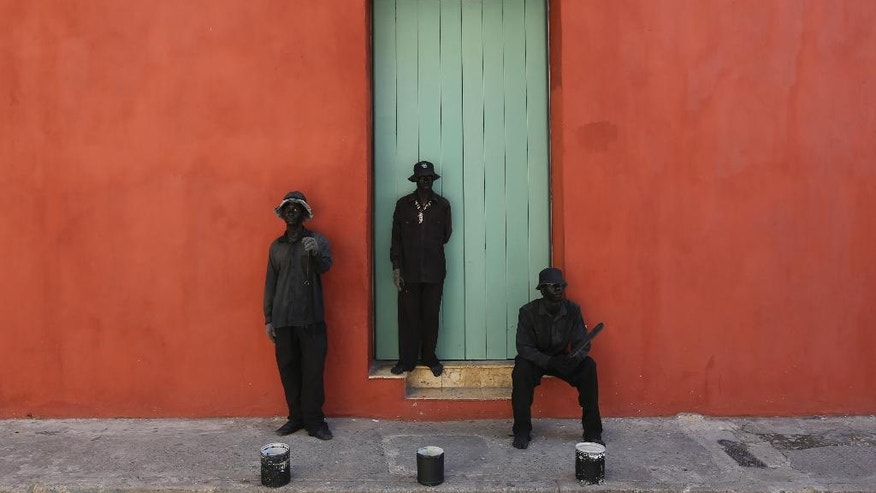 Street performers act as statues outside a home in the historical center of Cartagena, Colombia, Friday, Oct. 28, 2016. Cartagena is hosting the 25th Ibero-American Summit, an annual meeting of heads of state from Latin America and the Iberian Peninsula. (AP Photo/Fernando Vergara)