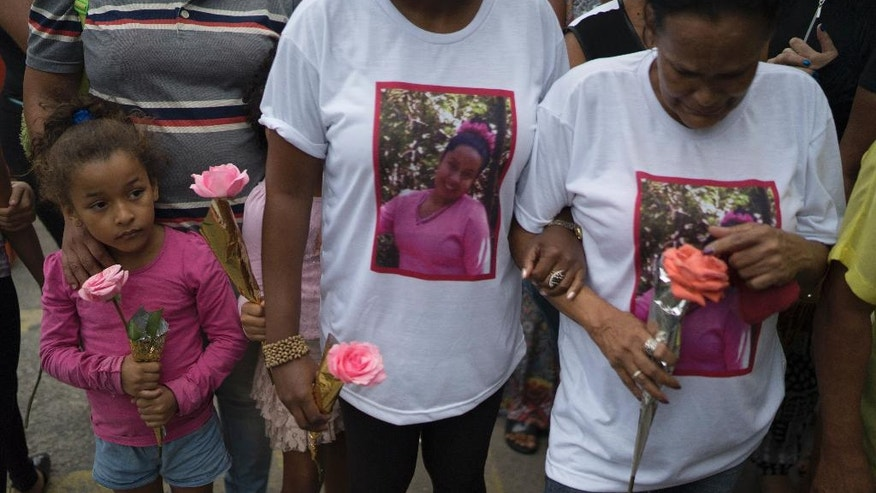 Relatives and friends hold roses during the burial service of Bruna Lace de Freitas, who was killed two days earlier by a stray bullet when she was inside her home, in Rio de Janeiro, Brazil, Friday, Oct. 28, 2016. The Brazilian Forum on Public Security says in its 10th annual report that in 2015 more people were murdered in Brazil than have been killed in war-torn Syria. (AP Photo/Leo Correa)