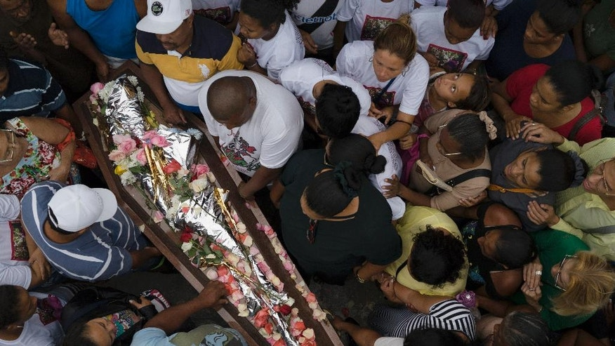 Relatives and friends gather round the coffin containing the remains of Bruna Lace de Freitas, who was killed two days earlier by a stray bullet when she was inside her home, in Rio de Janeiro, Brazil, Friday, Oct. 28, 2016. An anti-violence watchdog group says that in 2015 more people were murdered in Brazil than have been killed in war-torn Syria. (AP Photo/Leo Correa)