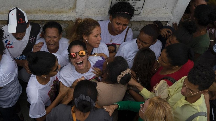 Vilma Carmo Lace, wearing sunglasses, expresses her grief during the burial of her sister Bruna Lace de Freitas, who was killed two days earlier by a stray bullet when she was inside her home, in Rio de Janeiro, Brazil, Friday, Oct. 28, 2016. An anti-violence watchdog group says that in 2015 more people were murdered in Brazil than have been killed in war-torn Syria. (AP Photo/Leo Correa)