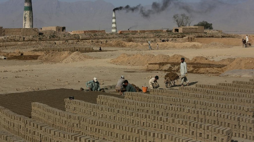 In this Oct. 3, 2016 photo, laborers work at a brick factory in  Deh Sabz on the outskirts of Afghanistan's capital, Kabul. Each month, Deh Sabz the district's 350 kilns produce an average of 700,000 bricks, which in a six-month season totals 4.2 million each. That's 245 million bricks from just one district of Kabul, all made by indentured laborers, some of them children as young as 4 or 5 years old. (AP Photo/Rahmat Gul)