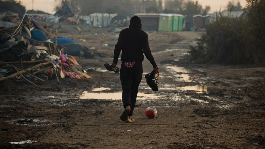 "A migrant kicks a ball as he past tents destroyed in the makeshift migrant camp known as ""the jungle"" near Calais, northern France, Friday, Oct. 28, 2016. Thousands of migrants dispersed this week from the now-torched camp they had called home in Calais are struggling to adapt to unfamiliar surroundings in towns and villages throughout France. (AP Photo/Emilio Morenatti)"