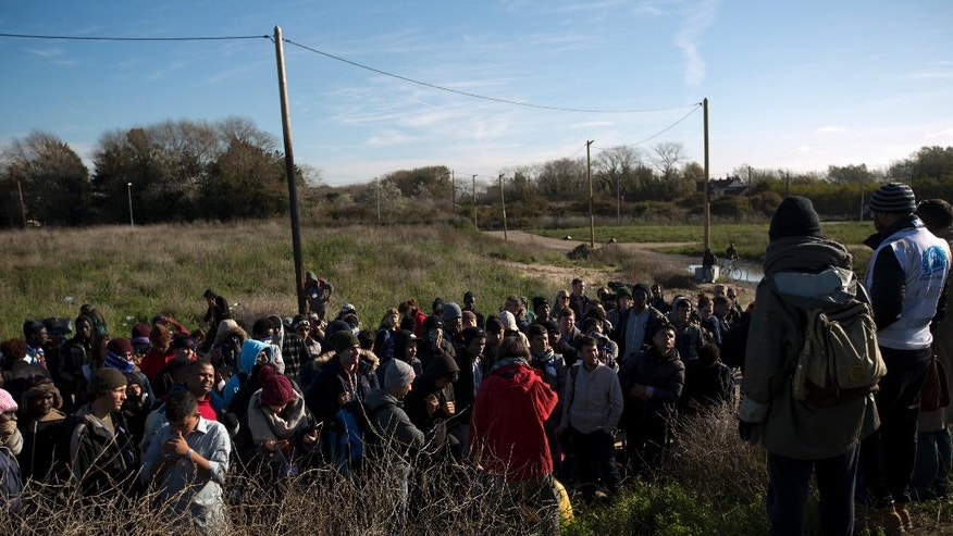 """Migrants receive instructions from ONG workers before getting on an official bus to take them away after being forced out from the makeshift migrant camp known as """"the jungle"""" near Calais, northern France, Friday, Oct. 28, 2016. Thousands of migrants dispersed this week from the now-torched camp they had called home in Calais are struggling to adapt to unfamiliar surroundings in towns and villages throughout France. (AP Photo/Emilio Morenatti)"""