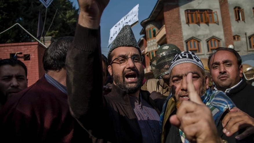 Kashmiri seaparatist leader, Mirwaiz Umar Farooq, shouts slogans during a protest march to the Grand mosque in Srinagar, Indian controlled Kashmir, Friday, Oct. 28, 2016. Authorities on Friday imposed curfew in some parts of Srinagar to foil a pro-freedom march to the Grand mosque called by separatist leaders. The march was called in protest after no one was allowed to pray inside the mosque on Fridays for nearly 16 weeks. (AP Photo/Dar Yasin)