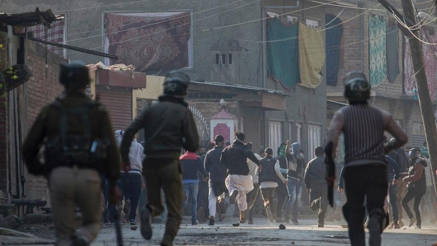 Indian paramilitary soldiers chase Kashmiri Muslim protesters during a protest in Srinagar, Indian controlled Kashmir, Friday, Oct. 28, 2016. Authorities on Friday imposed curfew in some parts of Srinagar to foil a pro-freedom march to the Grand mosque called by separatist leaders. The march was called in protest after no one was allowed to pray inside the mosque on Fridays for nearly 16 weeks. (AP Photo/Dar Yasin)