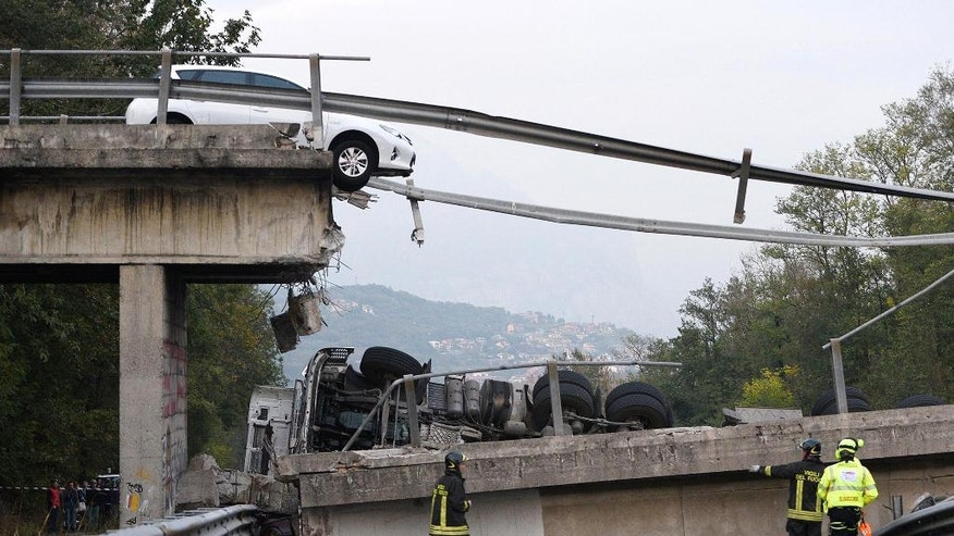 A car is stopped just where an overpass collapsed when a heavy truck, seen on the road below, was traveling on it, between Milan and Lecco, northern Italy, Friday, Oct. 28, 2016. An overpass north of Milan has collapsed under the weight of a truck carrying an over-size load just hours after highway authorities say they requested the road's immediate closure. (Fabrizio Cusa/ANSA via AP)