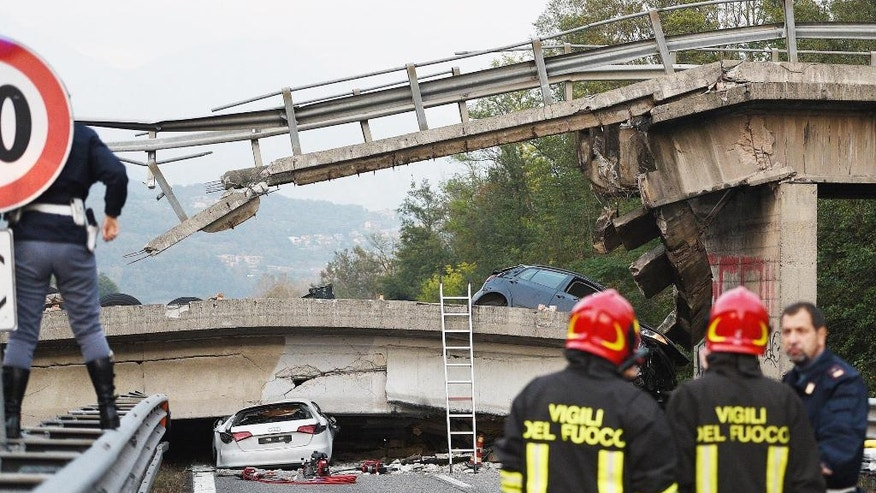 A car lies beneath an overpass after it collapsed when a heavy truck was traveling on it, between Milan and Lecco, northern Italy, Friday, Oct. 28, 2016. An overpass north of Milan has collapsed under the weight of a truck carrying an over-size load just hours after highway authorities say they requested the road's immediate closure. (Fabrizio Cusa/ANSA via AP)