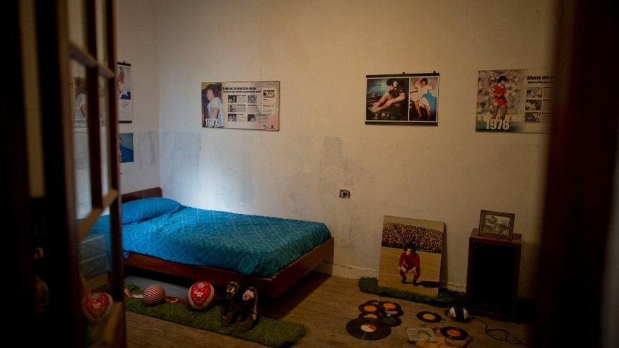 The bed and music records used by soccer legend Diego Armando Maradona decorate his old room on the upper floor of the home where he grew up in Buenos Aires, Argentina, Thursday, Oct. 27, 2016. The home where Maradona lived as a teenager while playing for Argentinos Juniors recently opened to the public, becoming a new shrine for the soccer legend. (AP Photo/Natacha Pisarenko)