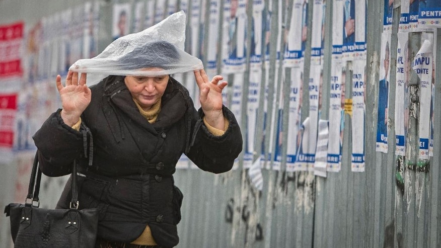 In this picture taken Wednesday, Oct. 26, 2016, a woman walks by electoral posters during a rainfall in Chisinau, Moldova. Moldovans will vote for a president Sunday for the first time in 20 years in an election which could move the former Soviet republic closer to Europe or rekindle the nation's old ties with Moscow as both Russia and the West seek greater influence over the strategically placed country of 4 million which signed an association agreement with the EU in 2014.(AP Photo/Roveliu Buga)