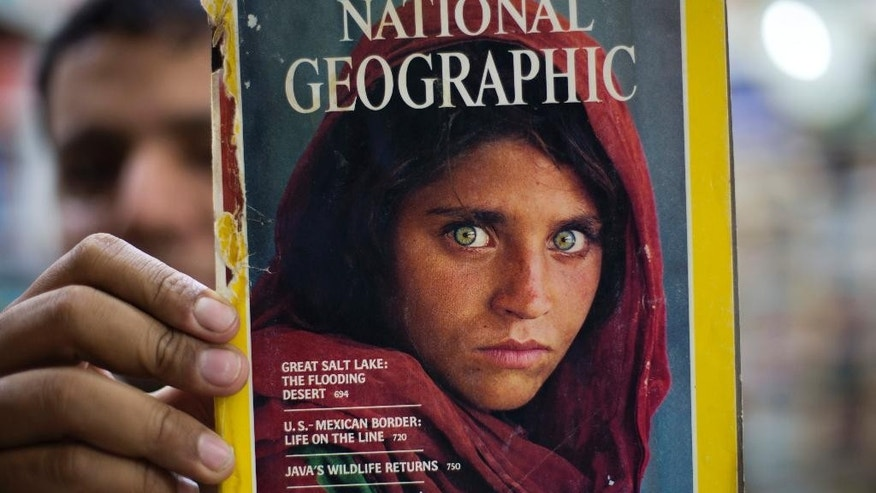 Pakistan's Inam Khan, owner of a book shop shows a copy of a magazine  with the photograph of Afghan refugee woman Sharbat Gulla, from his rare collection in Islamabad, Pakistan, Wednesday, Oct. 26, 2016. A Pakistani investigator says the police have arrested National Geographic's famed green-eyed 'Afghan Girl' for having a fake Pakistani identity card. Shahid Ilyas from the Federal Investigation Agency, says the police arrested Sharbat Gulla during a raid on Wednesday at a home in Peshawar. (AP Photo/B.K. Bangash)