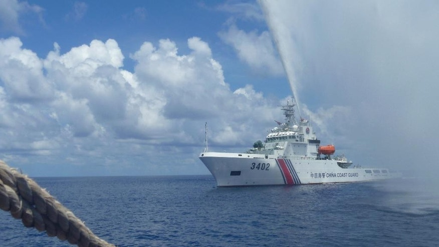 FILE - In this Sept. 23, 2015, file photo, Chinese Coast Guard members approach Filipino fishermen as they confront each other off Scarborough Shoal in the South China Sea, also called the West Philippine Sea. The Philippines and the U.S. are trying to verify a report that Chinese coast guard ships have left a disputed shoal, allowing Filipino fishermen back to the rich fishing area that China seized in 2012, triggering tensions in the South China Sea. (AP Photo/Renato Etac, File)