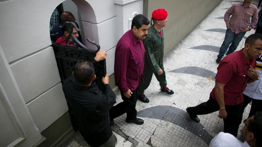 Venezuela's President Nicolas Maduro exits an area of Miraflores presidential palace to greet supporters in Caracas, Venezuela, Friday, Oct. 28, 2016.  For the most part, residents of Venezuela's capital ignored calls to stay home Friday to protest Maduro, handing a rare victory to the embattled leader. (AP Photo/Ariana Cubillos)