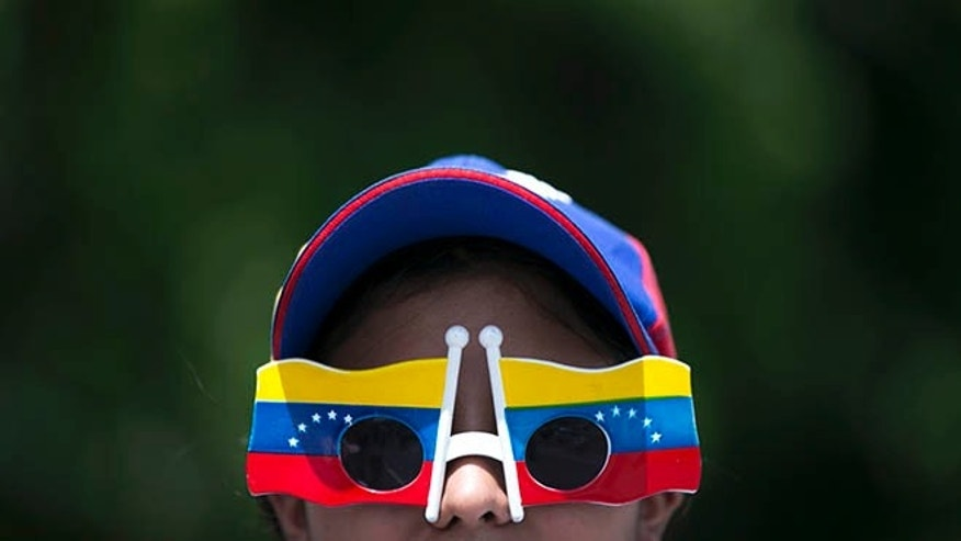 A woman wears Venezuelan flag motif glasses during a protest demanding a recall referendum against Venezuela's President Nicolas Maduro in Caracas, Venezuela, Saturday, Oct. 22, 2016. Venezuela is bracing for turbulence after the government blocked a presidential recall referendum in a move opposition leaders are calling a coup. The march was led by the wives of jailed activists. (AP Photo/Ariana Cubillos)