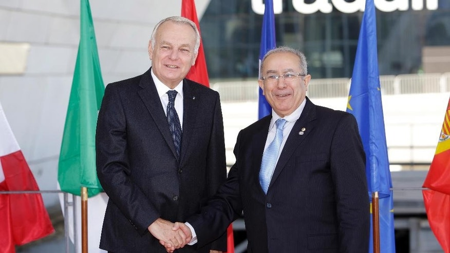 French Foreign Minister Jean-Marc Ayrault , left, welcomes Algeria's International Cooperation minister Ramtane Lamamra during a Mediterranean Summit 5+5, at the Villa Mediterranee in Marseille, southern France, Friday, Oct. 28, 2016. France is hosting an international summit of foreign ministers from countries near the western Mediterranean Sea that is expected to discuss the fight against the Islamic State group in Syria and elsewhere, radicalization, as well as migration. (AP Photo/Claude Paris)