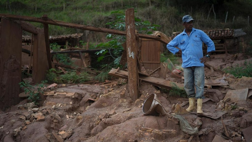 "In this Oct, 13, 2016 photo, Geraldo de Oliveira stands on the rubble of his home destroyed by a Nov. 5, 2015 mudslide unleashed by the bursting of a mine-waste basin, in Paracatu, Brazil. ""This place used to be a paradise. It was the most beautiful thing you've ever seen,"" said Oliveira. (AP Photo/Leo Correa)"