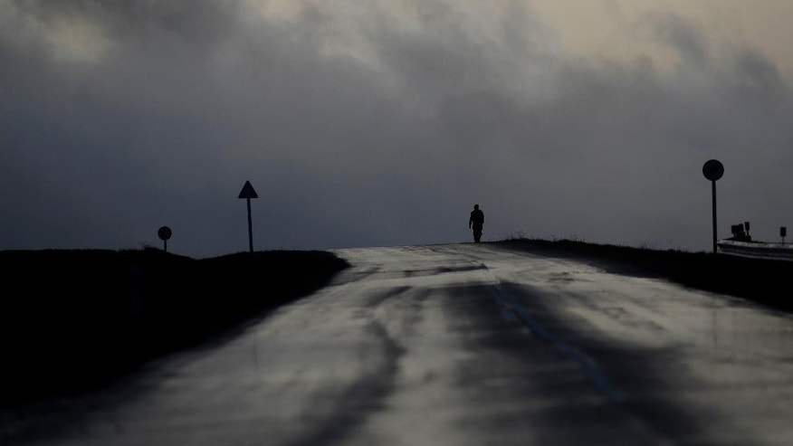 A walking man is silhouetted after a heavy rain in the village of Negnevichi, 130 km ( 81 miles ) west of the Belarus capital, Minsk, Saturday, Oct. 29, 2016. The air temperature is about 5 C (41 F). (AP Photo/Sergei Grits)