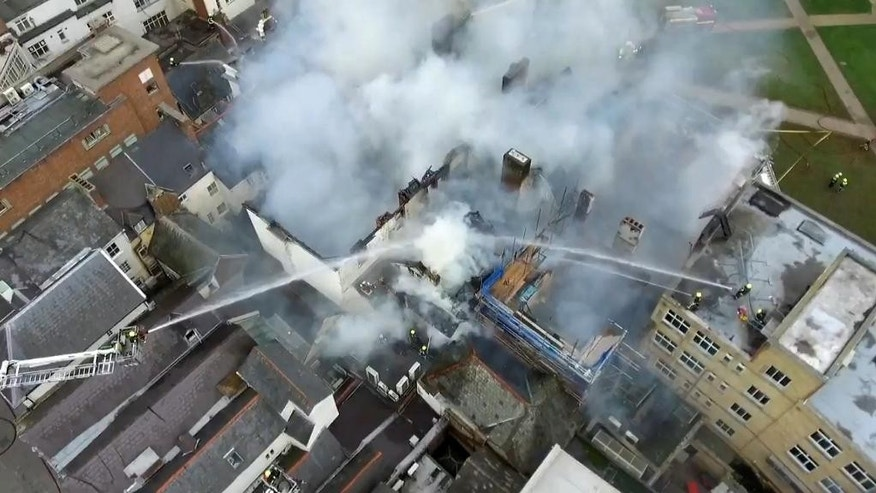 In this image made available by DC Police Drones, showing an aerial view of action as Devon & Somerset Fire & Rescue Service tackle a major fire at The Royal Clarence Hotel in Exeter, England, Friday Oct. 28, 2016.  According to the fire brigade, the fire may have started at an art gallery in Exeter city centre but spread to the nearby hotel, which is widely thought to be the oldest hotel in England. (DC PoliceDrones / PA via AP)