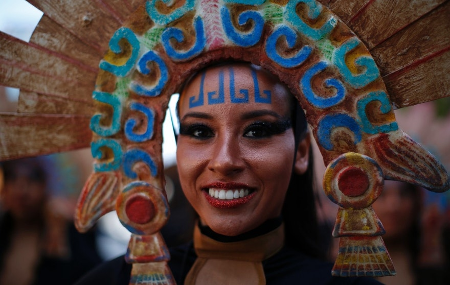 "A woman in costume smiles as she waits for the start of a Day of the Dead parade to begin along Mexico City's main Reforma Avenue, Saturday, Oct. 29, 2016. Mexico's Day of the Dead celebrations, which traditionally consisted of quiet family gatherings at the graves of their departed loved ones are fast changing under the influence of Hollywood movies, zombie shows, Halloween and even politics. Mexico's capital was holding its first Day of the Dead parade an idea actually born out of the imagination of a scriptwriter for last year's James Bond movie ""Spectre."" In the film, whose opening scenes were shot in Mexico City, Bond chases a villain through crowds of revelers in what resembled a parade of people in skeleton outfits and floats. (AP Photo/Dario Lopez-Mills)"
