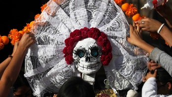 In this Thursday, Oct. 27, 2016 photo, residents work on a skeleton representation as part of the Day of the Dead festivities in Mexico City. The capital city will hold its first Day of the Dead parade Saturday, complete with floats, giant skeleton marionettes and over 1,000 actors, dancers and acrobats in costumes. (AP Photo/Marco Ugarte)