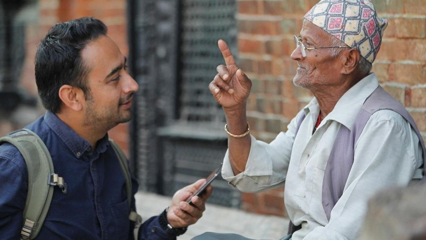 "In this Monday, Oct. 17, 2016 photo, Nepalese photographer Jay Poudyal chats with an elderly man in Kathmandu, Nepal. Inspired by the similar project ""Humans of New York,"" Poudyal has posted biographies and photographs for more than 800 Nepalis including villagers, bureaucrats, schoolchildren, housewives and students since launching his blog three years ago. Each morning, the 37-year-old college dropout takes to the streets of his native Kathmandu to chat with people, share jokes or heart-wrenching memories, and take their photos. (AP Photo/Niranjan Shrestha)"