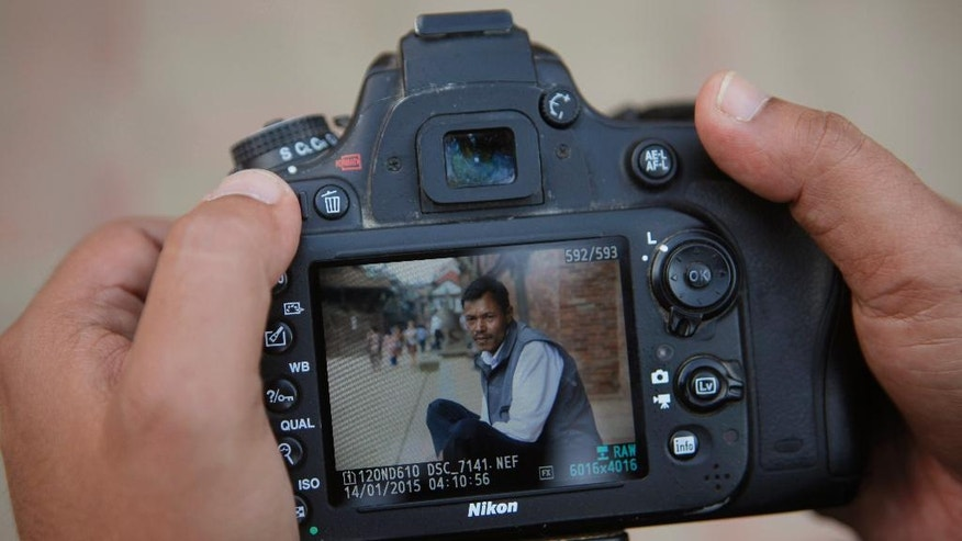"In this Monday, Oct. 17, 2016 photo, Nepalese photographer Jay Poudyal checks photos he took after chatting up different people in Lalitpur, Nepal. Inspired by the similar project ""Humans of New York,"" Poudyal has posted biographies and photographs for more than 800 Nepalis including villagers, bureaucrats, schoolchildren, housewives and students since launching his blog three years ago. (AP Photo/Niranjan Shrestha)"