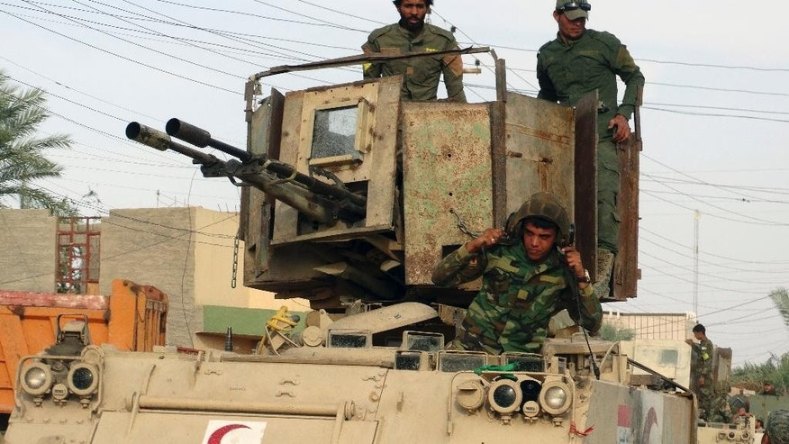 FILE - In this May 27, 2015 photo, Iraqi Shiite Hezbollah Brigade militiamen prepare their armored vehicles for fighting against the Islamic State group in the front line after regaining control of eastern Husaybah town, 8 kilometers (5 miles) east of Ramadi, Iraq. State-sanctioned Shiite militias launched an assault on the Islamic State group west of the Iraqi city of Mosul on Saturday, Oct. 29, 2016, but reiterated that they would not enter the Sunni majority city. Jaafar al-Husseini, a spokesman for the Hezbollah Brigades, said they launched an offensive Saturday along with other large militias toward the town of Tel Afar, which had a Shiite majority before it fell to IS in 2014. (AP Photo, File)