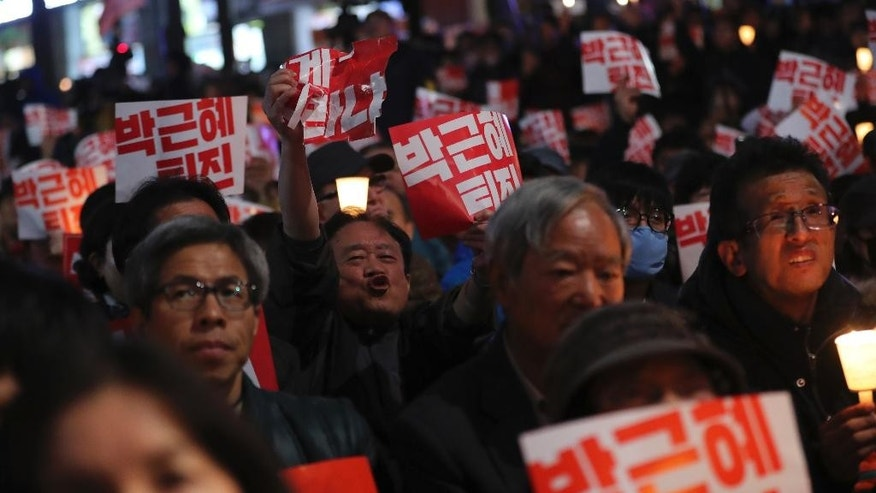 "South Koreans hold signs during a rally calling for President Park Geun-hye to step down in downtown Seoul, South Korea, Saturday, Oct. 29, 2016. Thousands of South Koreans took to the streets of the capital on Saturday calling for increasingly unpopular President Park Geun-hye to step down over allegations that she let an old friend, the daughter of a religious cult leader, interfere in important state affairs. The letters read ""Park Geun-hye step down."" (AP Photo/Lee Jin-man)"