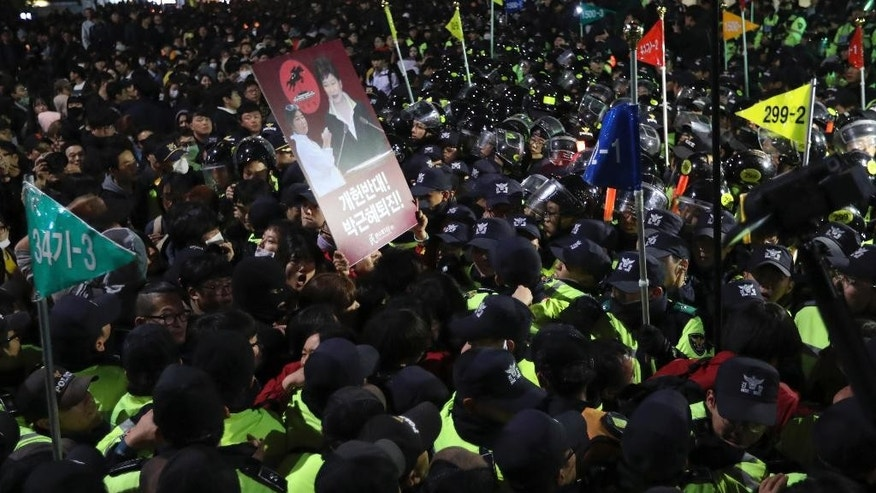 "South Korean protesters are blocked by police officers after a rally calling for President Park Geun-hye to step down in downtown Seoul, South Korea, Saturday, Oct. 29, 2016. Thousands of South Koreans took to the streets of the capital on Saturday calling for increasingly unpopular President Park Geun-hye to step down over allegations that she let an old friend, the daughter of a religious cult leader, interfere in important state affairs. The letters read ""Park Geun-hye step down."" (AP Photo/Lee Jin-man)"
