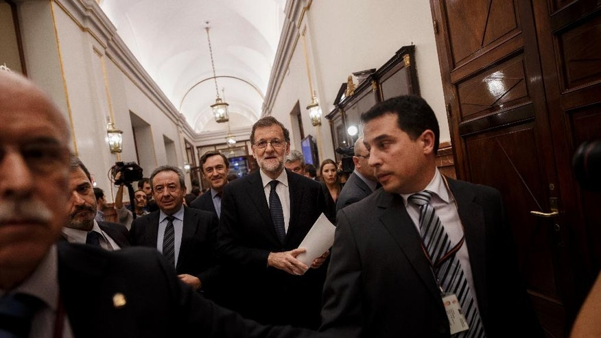 Spain acting conservative Prime Minister and Popular Party leader Mariano Rajoy is escorted by guards as he arrives for the investiture debate before the second confidence vote in Madrid, Spain, Saturday, Oct. 29, 2016. The Spanish Parliament will vote Saturday during an investiture debate that will likely end in the conservative Popular Party taking power, ending 10 months of political deadlock. (AP Photo/Daniel Ochoa de Olza)