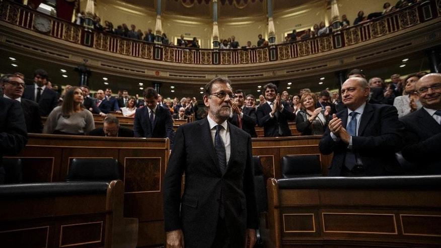 Newly re-elected Spain's Prime Minister Mariano Rajoy, centre, is apauded by lawmakers after the second and final confidence vote of the investiture debate at the Spanish Parliament in Madrid, Spain, Saturday, Oct. 29, 2016. The Spanish Parliament voted Saturday ending 10 months of political deadlock during which a caretaker government has run the country. (AP Photo/Daniel Ochoa de Olza,Pool)