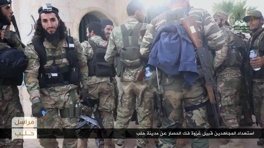 "This photo released online on Friday, Oct. 28, 2016, by the website of the al-Qaida-linked Fatah al-Sham, an anti-government militant group, shows fighters from the al-Qaida-linked Fatah al-Sham Front, preparing for the offensive on government positions in the northern Syrian province of Aleppo. Fierce fighting broke out around the northern Syrian city of Aleppo Friday as rebels announced a large-scale offensive to break the government's nearly two-month siege of opposition-held areas. Arabic, bottom, reads: ""Holy warriors getting ready for the battle to break the siege of Aleppo."" (militant photo via AP)"