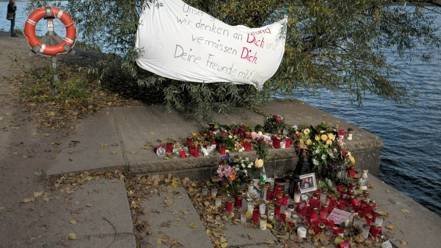 A banner, candles and flowers mark the spot where two teens were attacked in Hamburg.