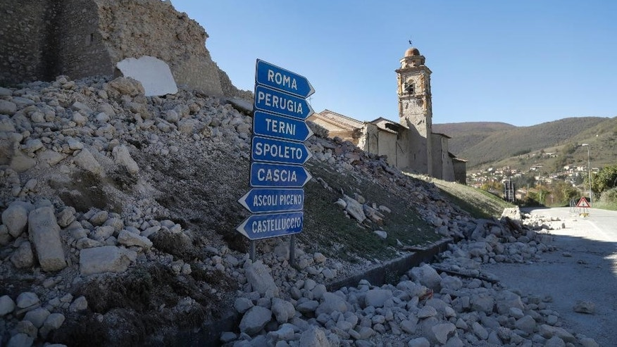 The tower of the Church of the Madonna of the Angels (Madonna degli Angeli) is still standing amidst rubble on a road near Norcia, central Italy, after an earthquake with a preliminary magnitude of 6.6 struck central Italy, Sunday, Oct. 30, 2016. A powerful earthquake rocked the same area of central and southern Italy hit by quake in August and a pair of aftershocks last week, sending already quake-damaged buildings crumbling after a week of temblors that have left thousands homeless. (AP Photo/Gregorio Borgia)