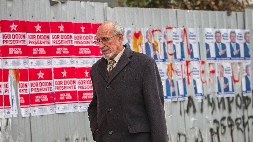 In this picture taken Wednesday, Oct. 26, 2016, a man walks by electoral posters in Chisinau, Moldova. Moldovans will vote for a president Sunday for the first time in 20 years in an election which could move the former Soviet republic closer to Europe or rekindle the nation's old ties with Moscow as both Russia and the West seek greater influence over the strategically placed country of 4 million which signed an association agreement with the EU in 2014.(AP Photo/Roveliu Buga)