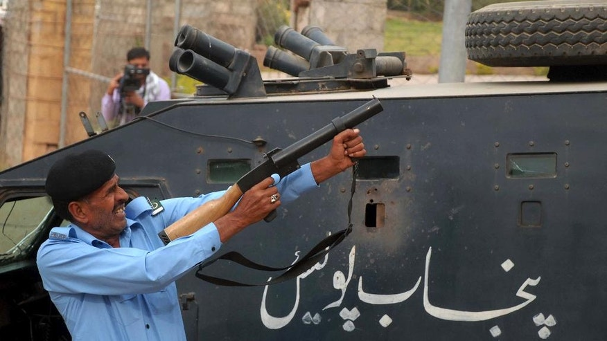 A Pakistani police officer fires tear gas shell to disperse supporters of Imran Khan, who are attempting to reach Khan's residence in Islamabad, Pakistan, Sunday, Oct. 30, 2016. Pakistani police used tear gas and batons to confront stone throwing supporters of cricketer-turned-politician Imran Khan, ahead of a planned protest next week. (AP Photo/Anjum Naveed)