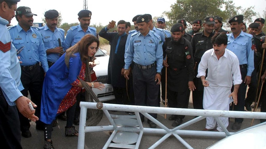 A supporter of Imran Khan tries to remove a police barrier set up  to stop supporters who are attempting to reach Khan's residence in Islamabad, Pakistan, Sunday, Oct. 30, 2016. Pakistani police used tear gas and batons to confront stone throwing supporters of cricketer-turned-politician Imran Khan, ahead of a planned protest next week. (AP Photo/Anjum Naveed)