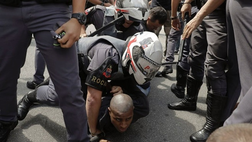 Police detain a man who was involved in a fight with supporters of U.S. presidential candidate Donald Trump in Sao Paulo, Brazil, Saturday, Oct. 29, 2016. The fight broke out during a small pro-Trump rally organized by a right-wing group via social media. (AP Photo/Andre Penner)