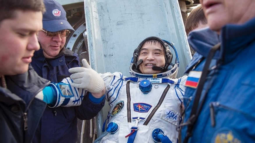 In this photo released by NASA,  Astronaut Takuya Onishi of the Japan Aerospace Exploration Agency (JAXA) is helped out of the Soyuz MS-01 spacecraft just minutes after the NASA astronaut Kate Rubins, and Russian cosmonaut Anatoly Ivanishin of Roscosmos landed in a remote area near the town of Zhezkazgan, Kazakhstan Sunday, Oct. 30, 2016. The Russian Soyuz space capsule has landed in Kazakhstan, bringing back three astronauts from the United States, Japan and Russia back to Earth from a 115-day mission aboard the International Space Station. (Bill Ingalls/NASA via AP)