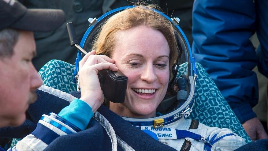 In this photo released by NASA, NASA astronaut Kate Rubins talks to her family via satellite phone shortly after she is helped out of the Soyuz MS-01 spacecraft along with Russian cosmonaut Anatoly Ivanishin of Roscosmos and astronaut Takuya Onishi of the Japan Aerospace Exploration Agency (JAXA) who landed in a remote area near the town of Zhezkazgan, Kazakhstan Sunday, Oct. 30, 2016. The Russian Soyuz space capsule has landed in Kazakhstan, bringing back three astronauts from the United States, Japan and Russia back to Earth from a 115-day mission aboard the International Space Station. (Bill Ingalls/NASA via AP)