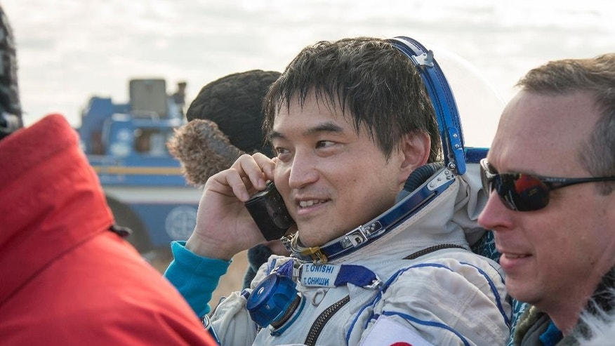 In this photo released by NASA, astronaut Takuya Onishi of the Japan Aerospace Exploration Agency (JAXA) talks on a satellite phone as he is carried into a medical tent out of the Soyuz MS-01 spacecraft just minutes after the NASA astronaut Kate Rubins, and Russian cosmonaut Anatoly Ivanishin of Roscosmos landed in a remote area near the town of Zhezkazgan, Kazakhstan Sunday, Oct. 30, 2016. The Russian Soyuz space capsule has landed in Kazakhstan, bringing back three astronauts from the United States, Japan and Russia back to Earth from a 115-day mission aboard the International Space Station. (Bill Ingalls/NASA via AP)